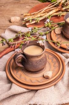 Heißes koffeinfreies natürliches chicorée-getränk in keramikbechern auf einem holztisch. gesunder alternativer ersatz für kaffee, koffein. blaue zichorienblüten, frische wurzeln, nahaufnahme