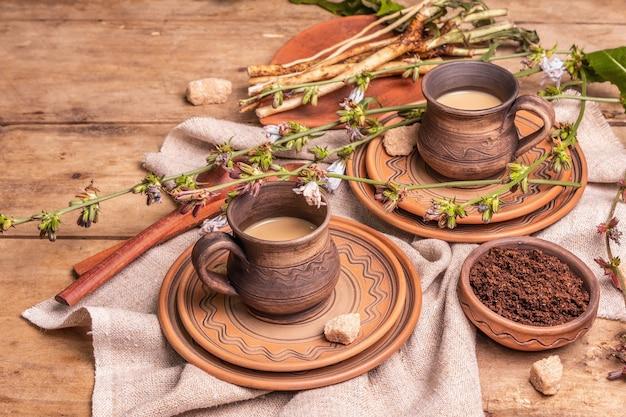 Heißes koffeinfreies natürliches chicorée-getränk in keramikbechern auf einem holztisch. gesunder alternativer ersatz für kaffee, koffein. blaue zichorienblumen, frische wurzeln, kopienraum
