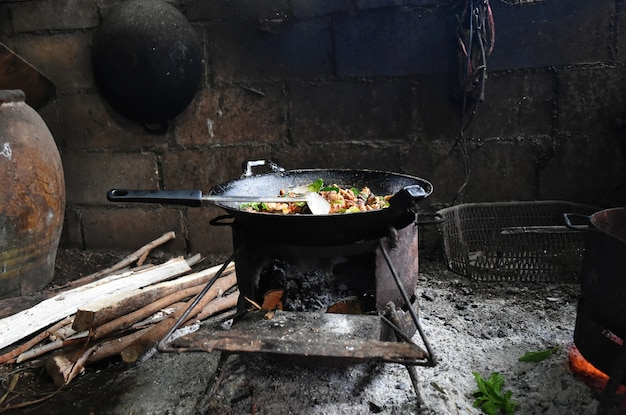 Heißes lebensmittel auf alter wanne auf altem ofen in der landschaft in nord von thailand