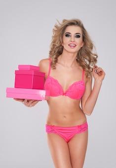 Heißes mädchen in rosa dessous, die stapel von geschenken halten