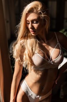 Heißes porträt der schönen sinnlichkeitsfrau in der weißen spitzenwäsche ruhen im raum bei sonnenlicht. weibliche sinnliche spitzenunterwäsche