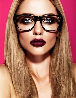 Heißes schönes blondes frauenmodell mit frischem täglichem make-up mit dunkelvioletter lippenfarbe und sauberer gesunder haut in gläsern
