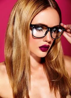Heißes schönes blondes frauenmodell mit frischem täglichem make-up mit dunkler lippenfarbe und sauberer gesunder haut auf rotem hintergrund in gläsern