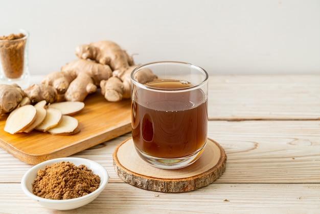 Heißes und süßes ingwersaftglas mit ingwerwurzeln - gesunder getränkestil