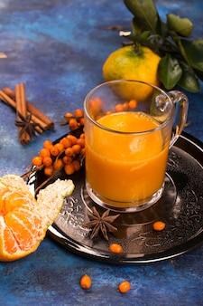 Heißes vitaminreiches getränk mit mandarine, sanddorn und gewürzen.