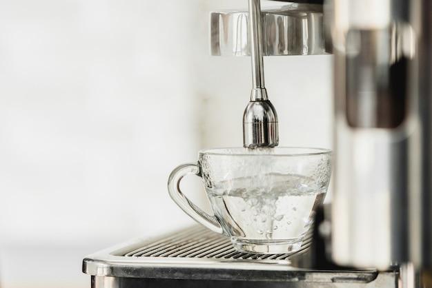 Heißes wasser aus der kaffeemaschine fließt in die tasse für die herstellung von americano