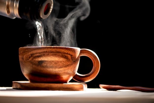 Heißes wasser in die kaffeetasse gießen