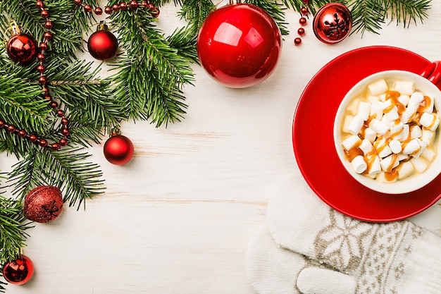 Heißes weihnachtsgetränk in der roten tasse kakao mit marshmallow-schokoladenzimt und weihnachtsdekorationen auf einer hölzernen hintergrundoberansicht