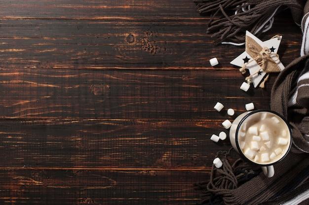 Heißes weihnachtsgetränk mit eibischen in einem eisenbecher, auf einem holztisch und einem schal. , urlaub, grußkarte exemplar.