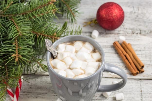 Heißes wintergetränk. heiße weihnachtsschokolade oder kakao mit marshmallow auf weißem holztisch mit weihnachtsschmuck