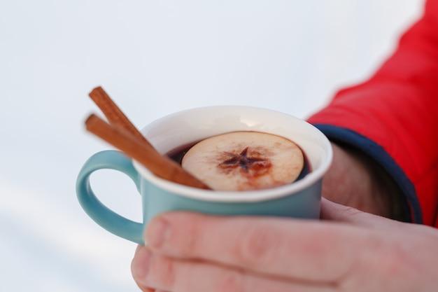Heißes wintergetränk im wald, glühwein in den händen