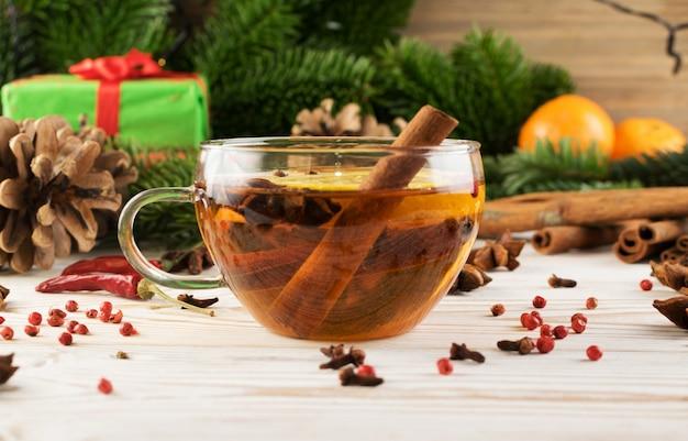 Heißes wintergetränk mit gewürzen und weihnachtsdekoration
