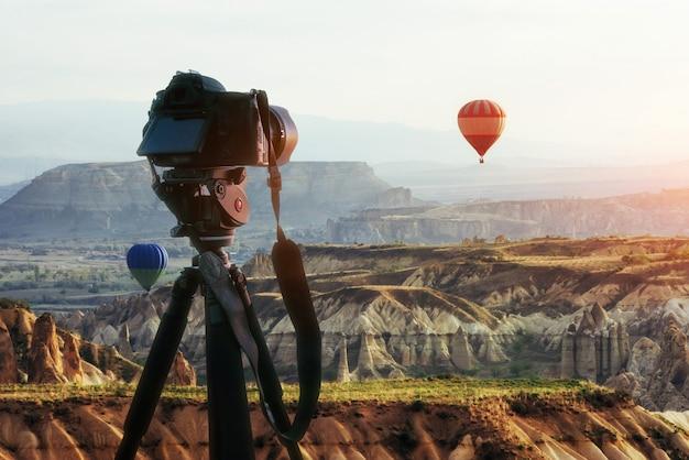 Heißluftballon, der über felsenlandschaft bei der türkei fliegt. dslr-kamera auf einem stativ im vordergrund