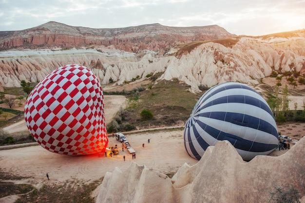 Heißluftballon, der über felsenlandschaft bei der türkei fliegt. kappadokien