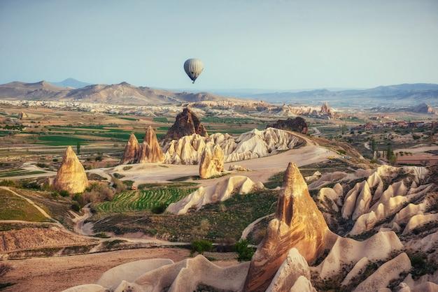 Heißluftballon, der über felsenlandschaft bei kappadokien türkei fliegt.
