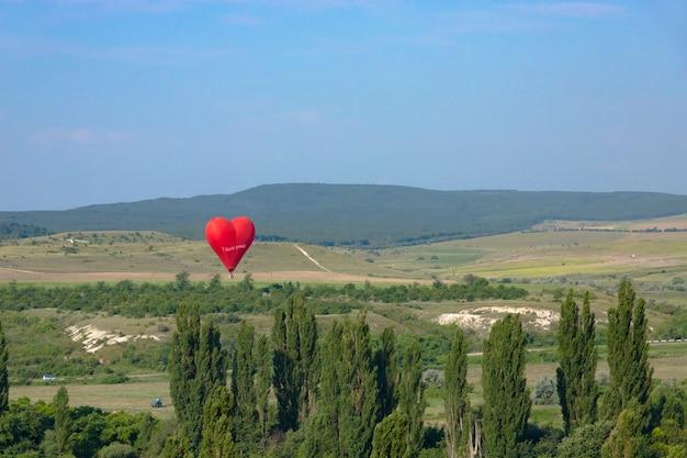 Heißluftballon roter ballon in form eines fliegenden herzens vor dem hintergrund des weißen felsens