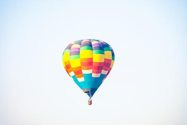 Heißluftballon über dem grünen reisfeld. zusammensetzung der natur und des weißen hintergrunds.