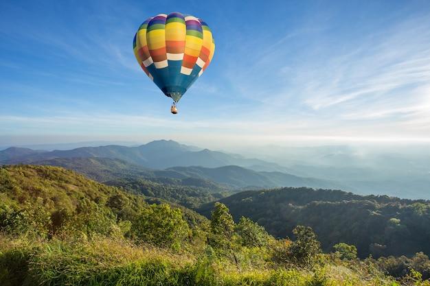 Heißluftballon über hohem berg bei sonnenuntergang