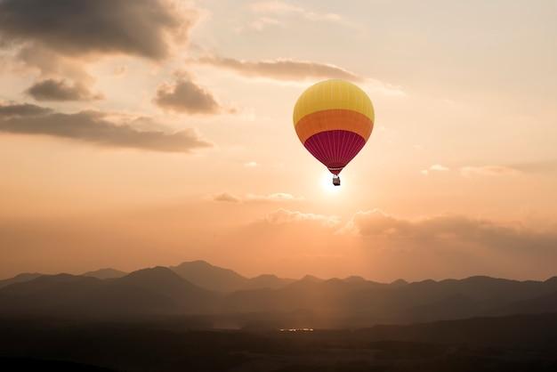 Heißluftballone, die über berg mit dem sonnenaufgang im himmel fliegen.