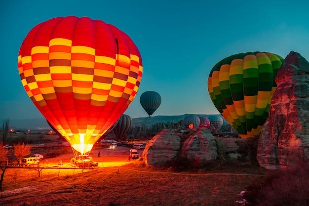 Heißluftballons bei sonnenaufgang bereiten sich auf den flug vor.