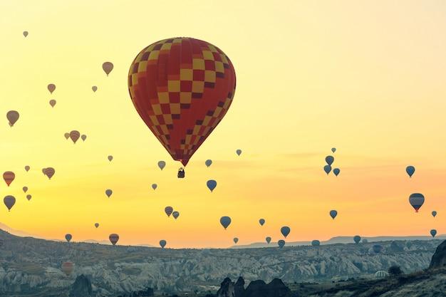 Heißluftballons steigen bei sonnenaufgang auf. kappadokien ist weltweit als einer der besten orte zum fliegen mit heißluftballons bekannt.