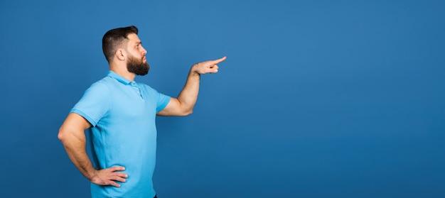 Heiter. porträt des kaukasischen schönen mannes isoliert auf blauer wand mit exemplar. männliches model mit bart.