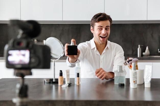 Heitrer junger mann, der seine videoblogepisode filmt