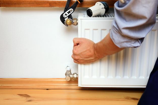 Heizkörpernahaufnahme reparieren. mann repariert kühler mit schraubenschlüssel. luft aus dem kühler entfernen