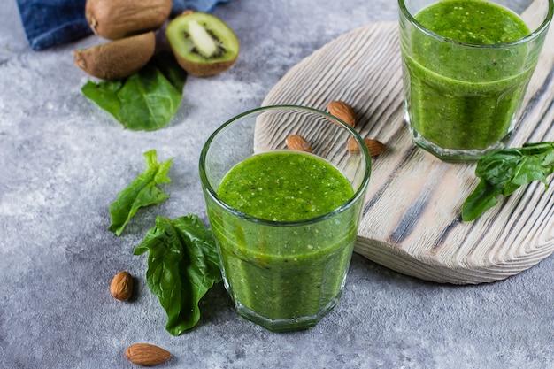 Helathy green smoothie mit grünem apfel, spinat, kiwi und mandelnüssen auf grauem konkretem hintergrund.