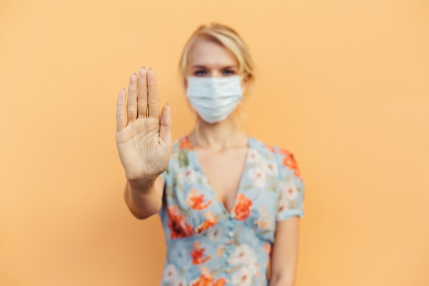 Helfen sie dabei, die weltweite ausbreitung des ausbruchs einer infektionskrankheit mit koronaviren zu stoppen. auf hintergrund frau in maske fokus auf gestreckte hand als symbol für abstand halten vermeiden kommunikation, gesundheitskonzept