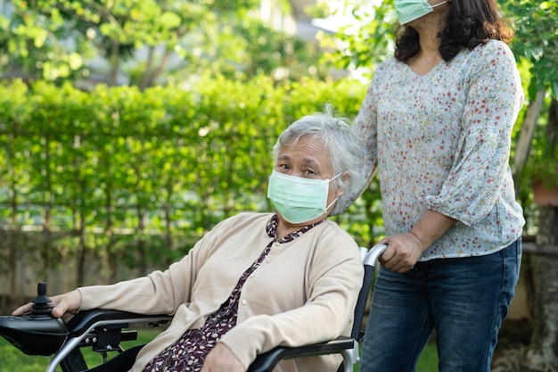 Helfen sie einer asiatischen seniorin auf einem elektrischen rollstuhl und tragen sie eine maske zum schutz des coronavirus im park