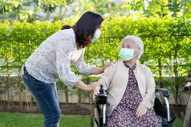 Helfen sie einer asiatischen seniorin auf einem elektrorollstuhl und tragen sie eine maske zum schutz des covid19-coronavirus