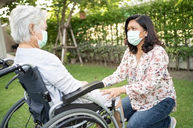 Helfen sie einer asiatischen seniorin im rollstuhl und tragen sie eine maske zum schutz des covid19-coronavirus im park