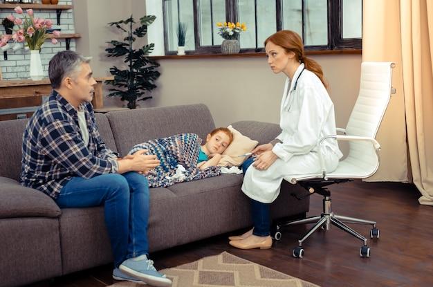 Helfen sie ihr bitte. trauriger besorgter mann, der auf dem sofa in der nähe seiner tochter sitzt, während er mit dem arzt spricht