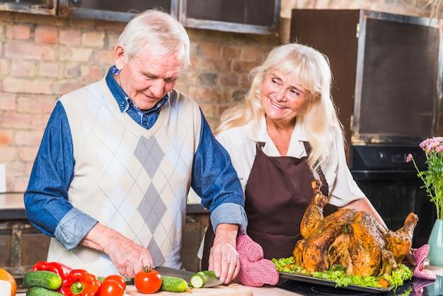 Helfende frau des älteren mannes mit dem kochen des truthahns