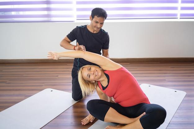 Helfende frau des ausbilders, zum der seitenbiegung an der yogaklasse zu tun