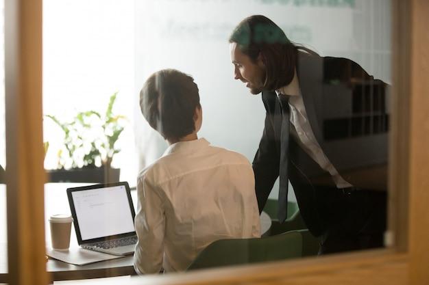 Helfende geschäftsfrau des geschäftsmannes, die e-mail auf laptop, hintere ansicht bespricht