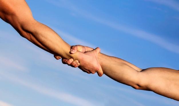 Helfende hand konzept und internationaler tag des friedens, unterstützung. zwei hände, helfender arm eines freundes, teamwork.