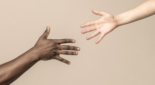 Helfende hand, rettung, multiathnische leute. helfende hände, rettungsgeste. schwarze und weiße menschliche hände. afrikanische und kaukasische hände. einem anderen eine helfende hand geben. frau und afrikanische frauenhand