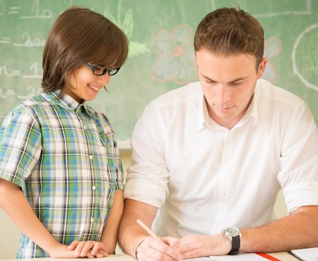 Helfende kinder des männlichen lehrers im klassenzimmer während der klasse