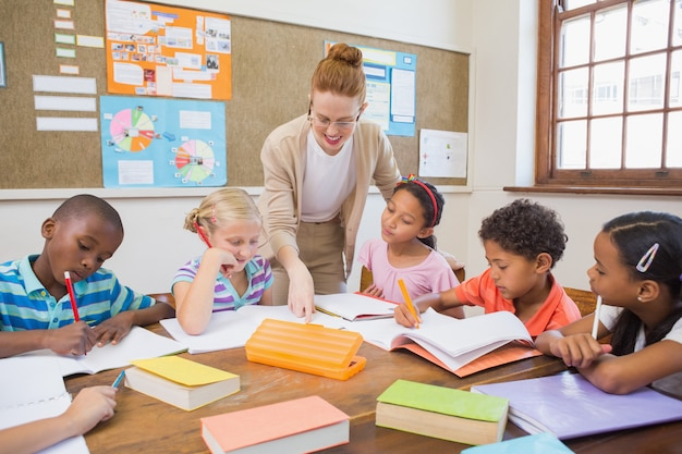 Helfende schüler des hübschen lehrers im klassenzimmer