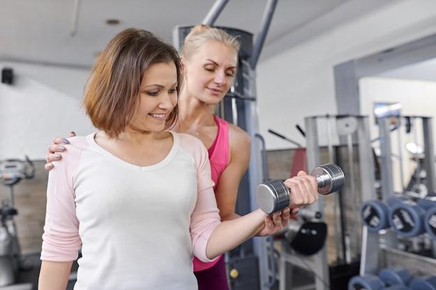 Helfende sommerfrau des persönlichen eignungslehrers, die im fitnessstudio trainiert.