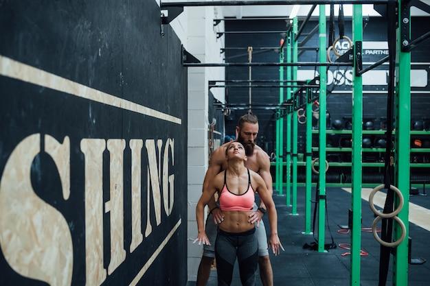 Helfende sportlerin des trainers des jungen mannes, die gymnastischen ring erreicht