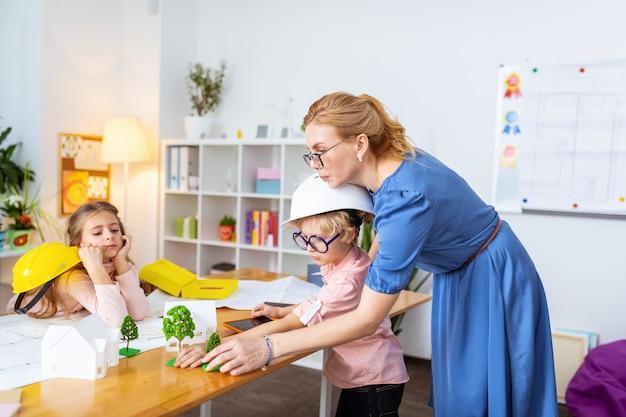 Helfender blonder junge. der lehrer hilft dem blonden jungen, ein baummodell in ihre intelligente stadt zu bringen, während er hausmodellierung studiert