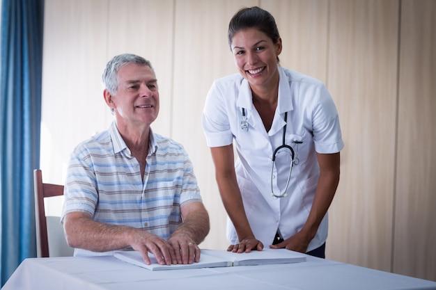 Helfender patient der ärztin beim ablesen des blindenschrift-buches