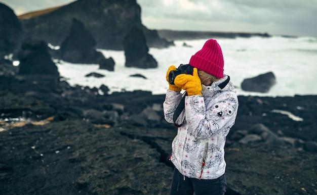 Hell gekleidete junge frau touristin macht ein foto von einer schönen seelandschaft, die am ufer mit schwarzem vulkansand bei bewölktem wetter steht.