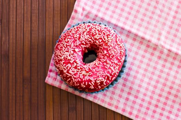 Hell rosa donut auf einem braunen hölzernen hintergrund
