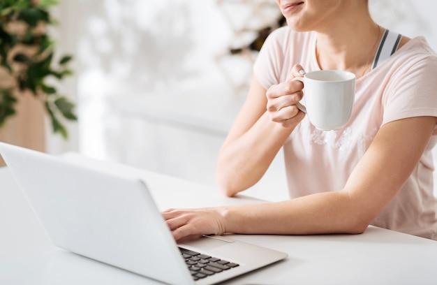 Hell und frisch. erfreut entspannte, wunderschöne dame, die einen kaffee trinkt und mit ihrem laptop am tisch einige rezepte durchblättert