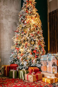 Hell weihnachtsbaum in einem raum mit rotem teppich mit vielen geschenken