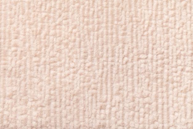 Hellbeiger flauschiger hintergrund aus weichem, flauschigem stoff. beschaffenheit der textilnahaufnahme.